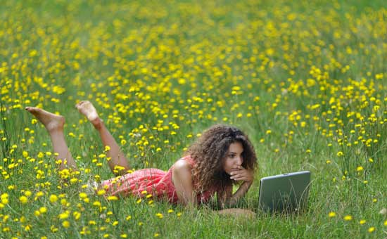 Woman Using Laptop in Field